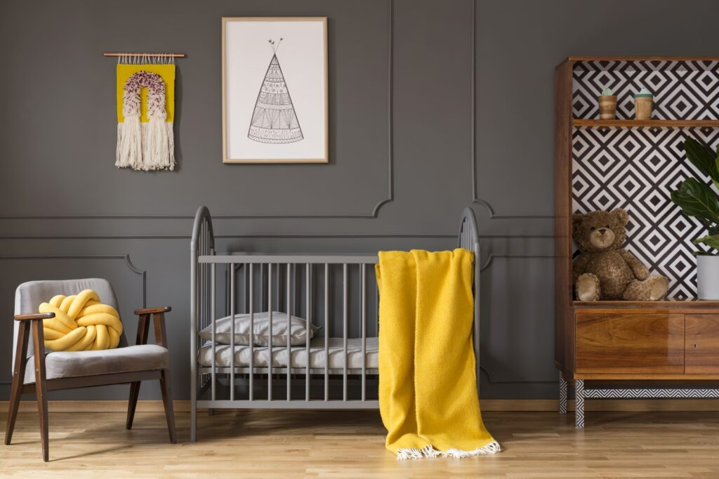 real photo of a baby cot with yellow cot standing between an armchair and a cupboard with teddy bear and a plant in child's room interior