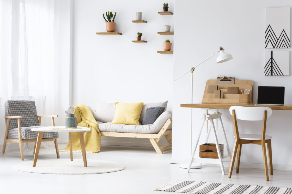 wooden chair at desk with laptop and lamp in white apartment interior with armchair real photo
