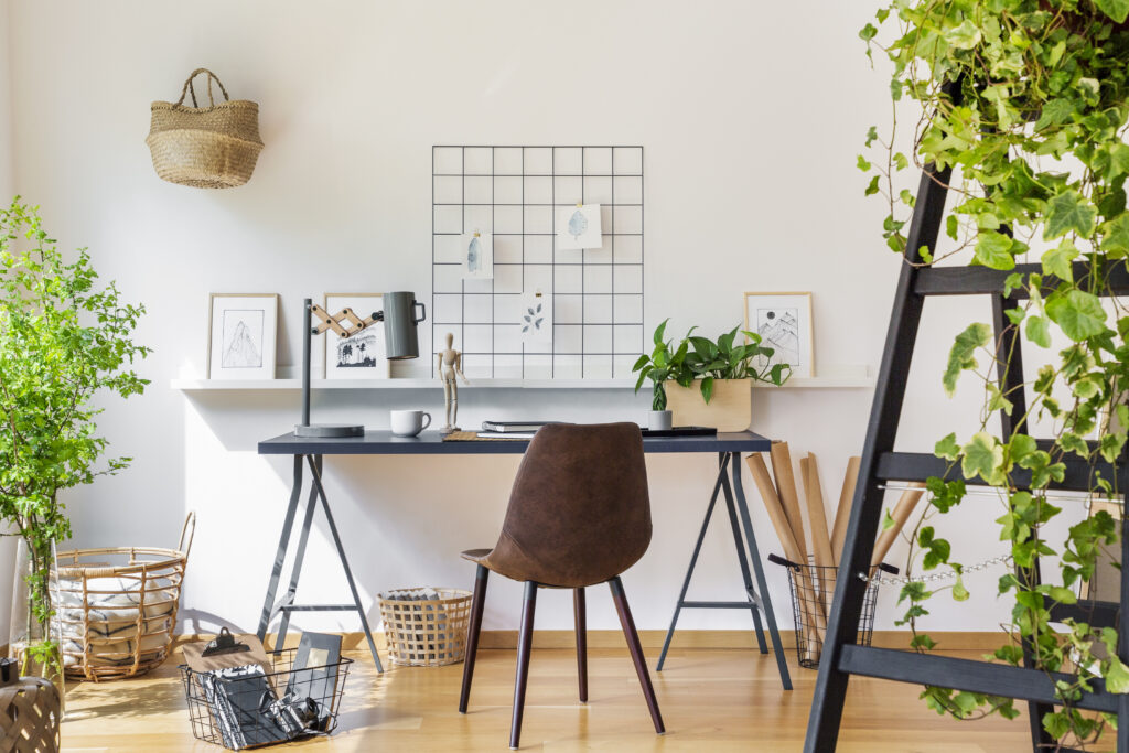 brown chair at desk in white boho home office interior with plants and posters real photo
